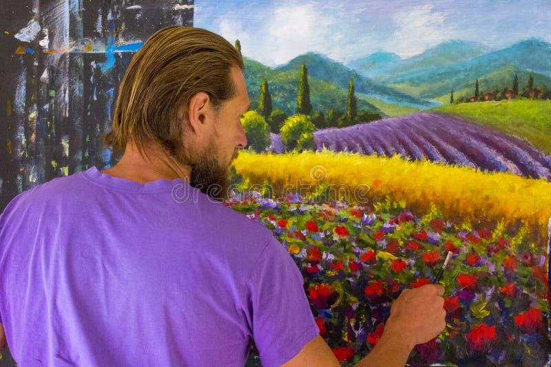 Процесс искусства творческий Художник создает крася итальянскую сельскую местность лета Тоскана Поле красных маков, поле желтой р стоковое изображение