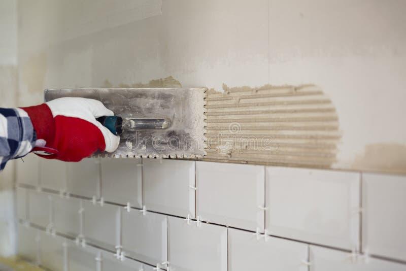 Процесс крыть плитки черепицей в кухне Улучшение дома, re стоковое изображение rf