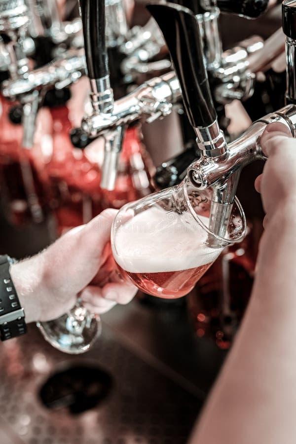 Процесс лить бледное пиво через fount стоковая фотография rf