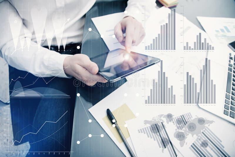 Процесс менеджера банкира работая Диаграммы рынка работы торговца аналитика фото Используя электронные устройства Графические зна стоковые фотографии rf