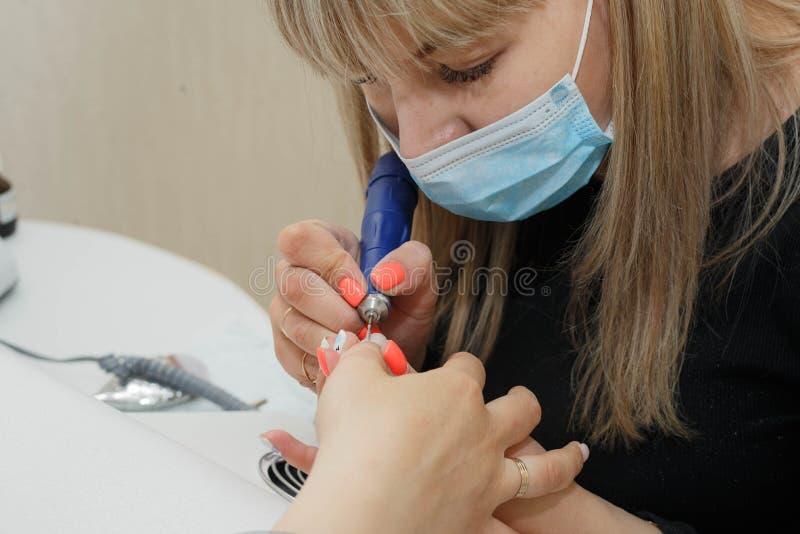 Процесс очищать ноготь от старого покрытия, выравнивания и давать ему пожеланную форму стоковые изображения rf