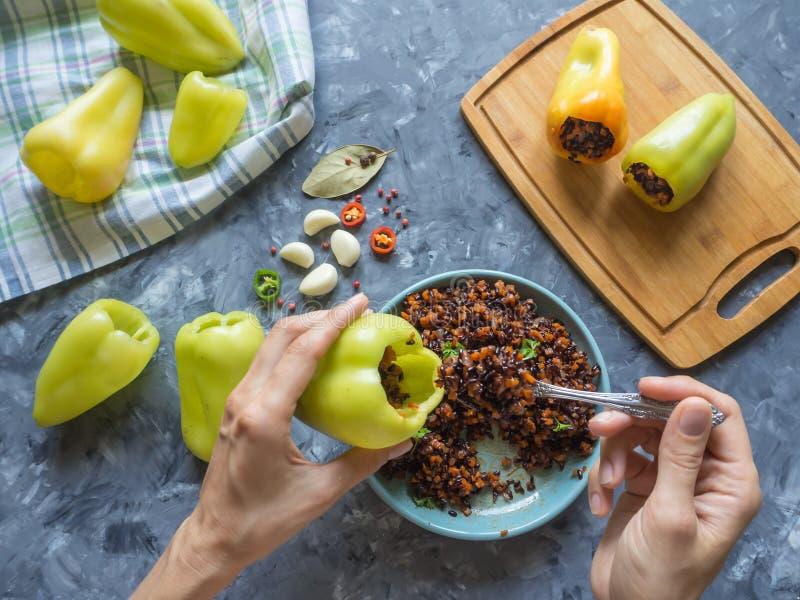 Процесс подготавливать заполненные перцы с черными рисом и овощами Вегетарианские натуральные продукты стоковое изображение