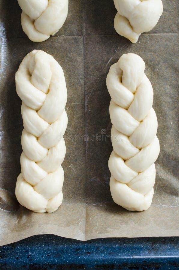 Процесс подготовки - сырцовые unbaked плюшки Плюшки теста дрожжей на печь бумаге, конце-вверх стоковая фотография
