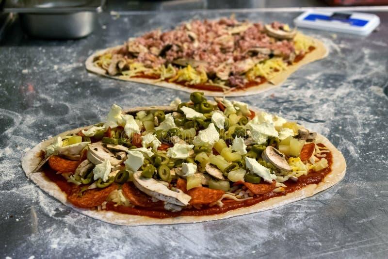 Процесс приготовления и приготовления пиццы в ресторане стоковые фотографии rf