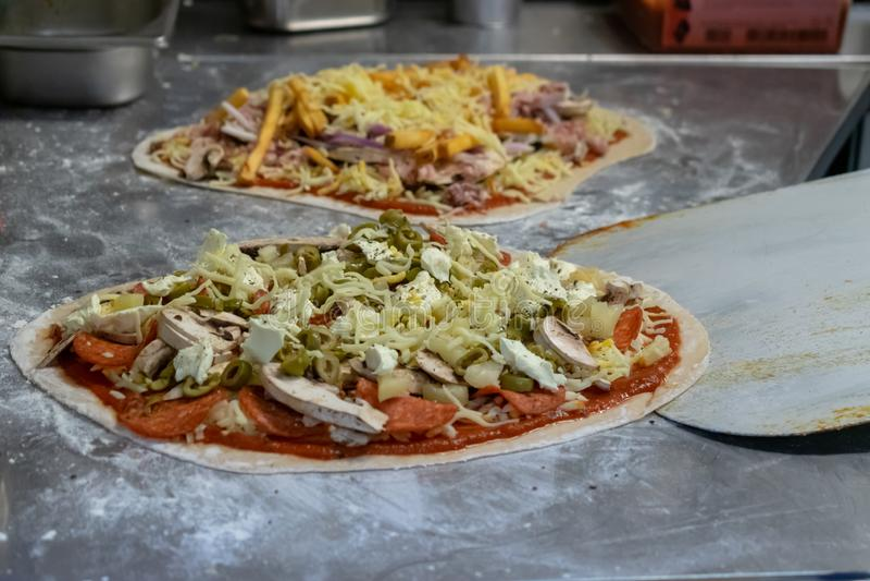 Процесс приготовления и приготовления пиццы в ресторане стоковая фотография