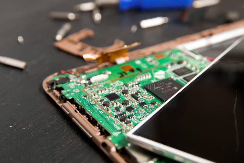 Процесс ремонта прибора таблетки ПК около отвертки и сдержанного на черной деревянной предпосылке демонтировано Сломленное стекло стоковое изображение