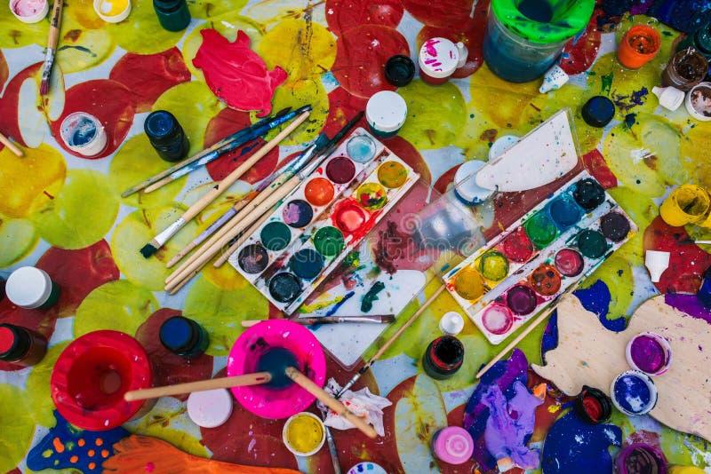 Процесс рисовать и создания творческие способности Большая таблица на которой щетки, краски, консервные банки воды и палитра стоковая фотография