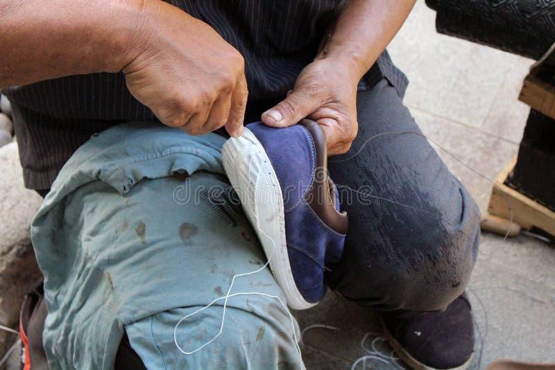 Процесс ручной репарации, подошвы и ранта ботинка фиксируя и шить стоковая фотография