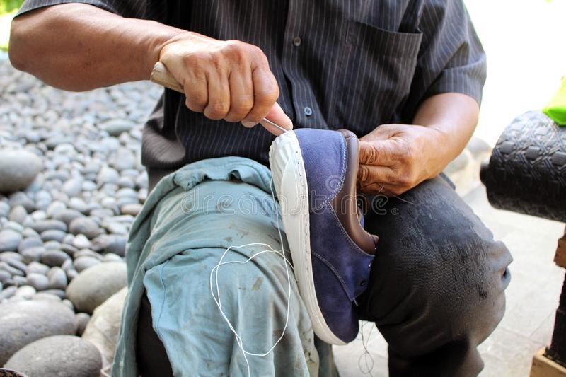 Процесс ручной репарации, подошвы и ранта ботинка фиксируя и шить стоковые фото