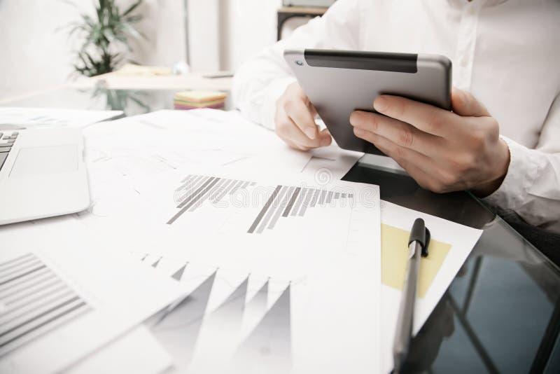 Процесс управляющего рисками работая Таблетка работы торговца фото современная Касающее электронное устройство График, оценка фон стоковые фото