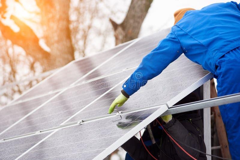 Процесс устанавливать голубые солнечные модули на крыше современного здания во время времени зимы снежного стоковое изображение rf