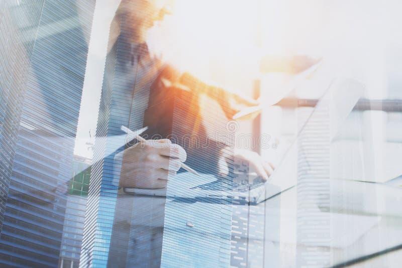 Процесс Coworking на солнечном офисе 2 сотрудника используя компьютер на солнечном офисе Двойная экспозиция, здание небоскреба стоковая фотография rf