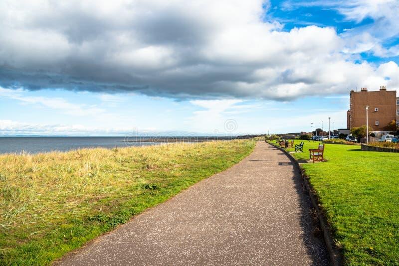 Прошлый побережья выровнянное с деревянными скамьями и голубым небом с облаками стоковая фотография rf