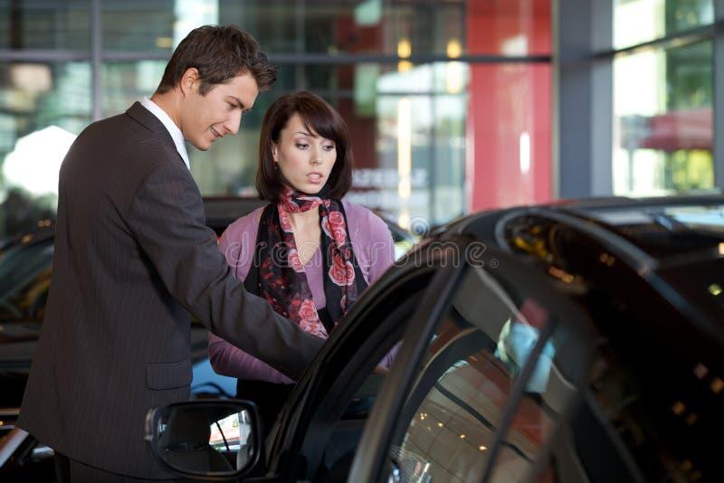 Продавец автомобилей объясняя характеристики автомобиля к клиенту стоковые фотографии rf