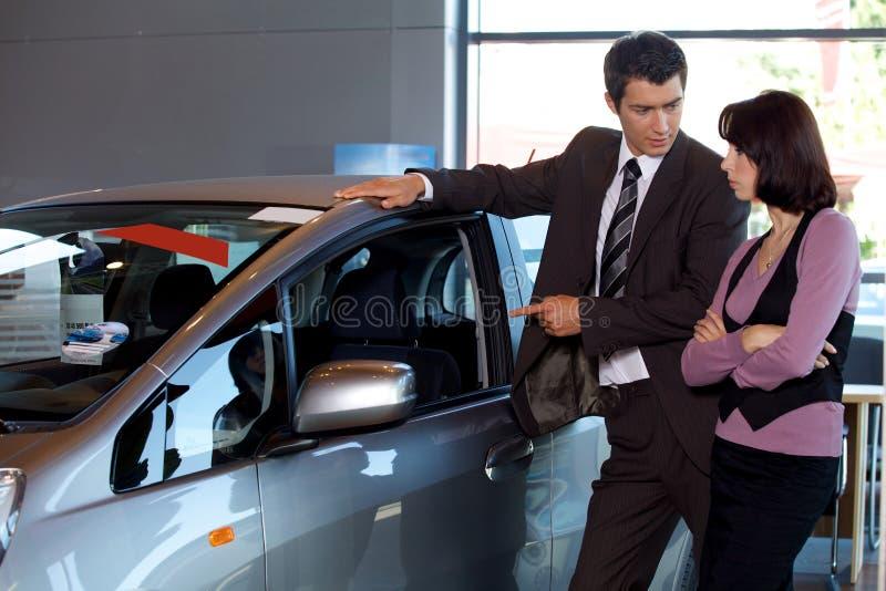 Продавец автомобилей объясняя характеристики автомобиля к клиенту стоковая фотография rf