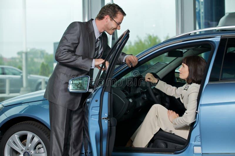Продавец автомобиля объясняя характеристики автомобиля к клиенту стоковое изображение