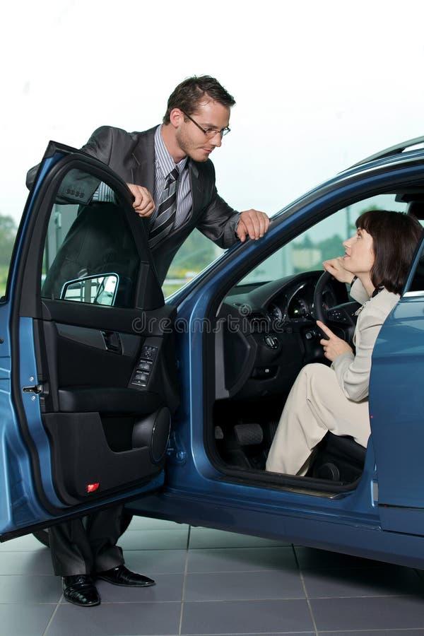 Продавец автомобиля объясняя характеристики автомобиля к клиенту стоковое изображение rf