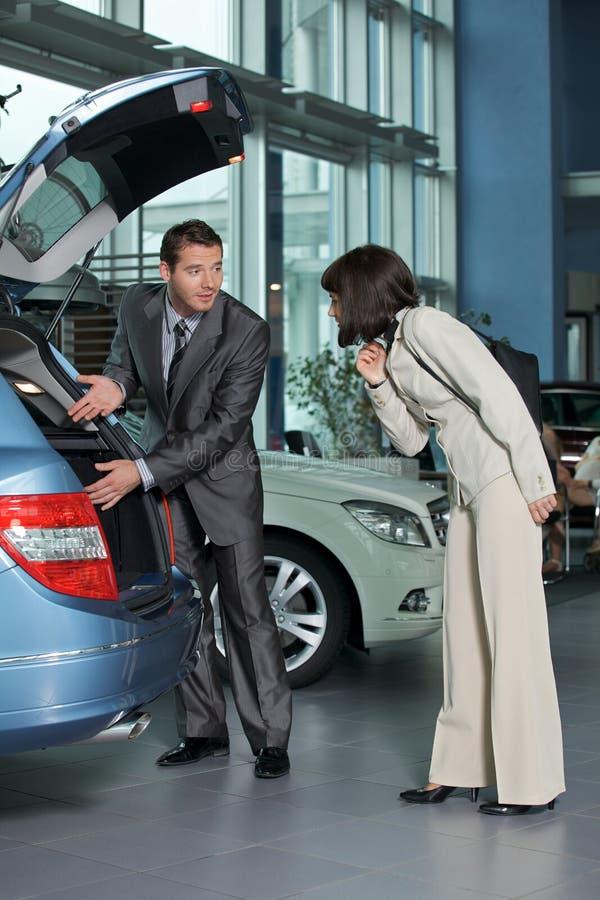 Продавец автомобиля показывая характеристики автомобиля к клиенту стоковые фотографии rf