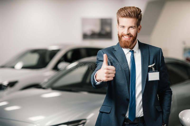 Продавец в костюме показывая большой палец руки вверх и смотря камеру стоковое изображение rf