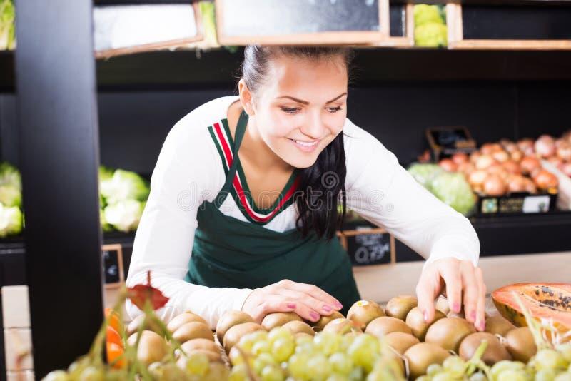 Продавец женщины устанавливая кивиы стоковое изображение
