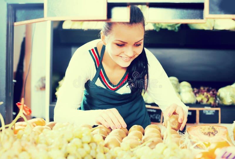 Продавец женщины устанавливая кивиы стоковое изображение rf