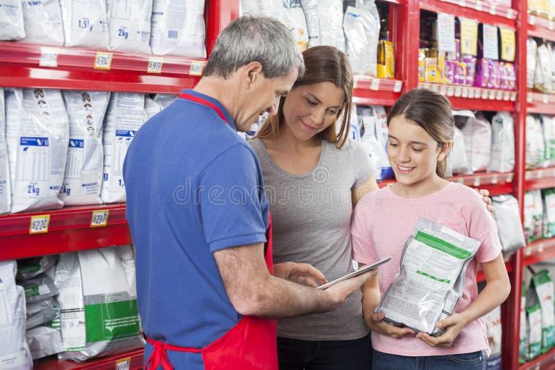 Продавец используя таблетку цифров пока помогающ семье в любимчике Stor стоковая фотография rf