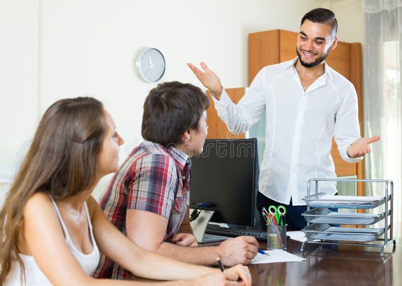 Продавец и пары в офисе стоковое фото rf