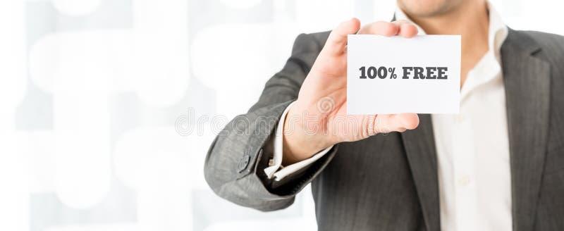 Продавец показывая белую визитную карточку с знаком 100% свободным стоковые изображения
