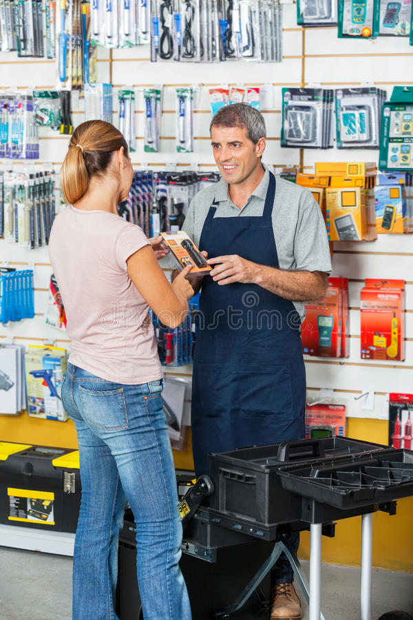 Продавец показывая электрофонарь к клиенту внутри стоковые фотографии rf