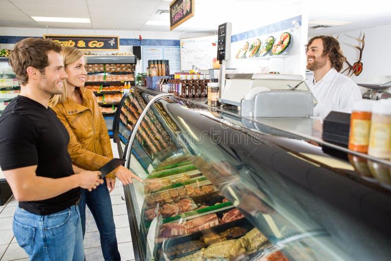 Продавец присутствуя на клиентах на магазине мясника стоковое фото