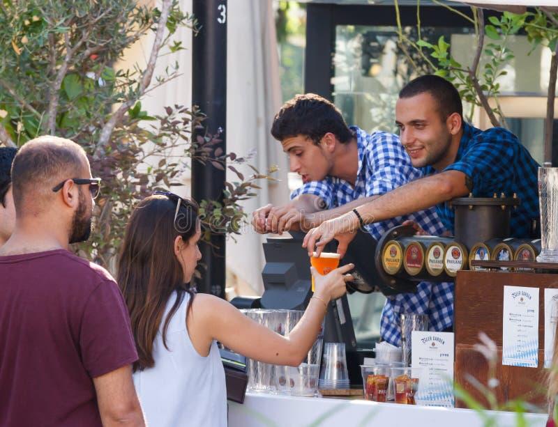 Продавец связывает с гостем фестиваля на ежегодном festiv пива стоковая фотография