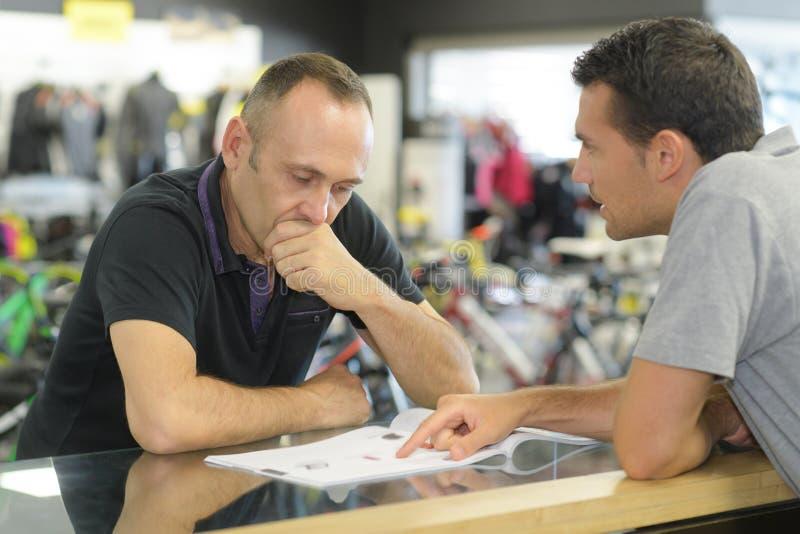 Продавец спрашивая, что человек подписал получение в магазине стоковые фото