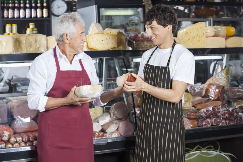 Продавцы держа сыр пока смотрящ один другого стоковая фотография rf