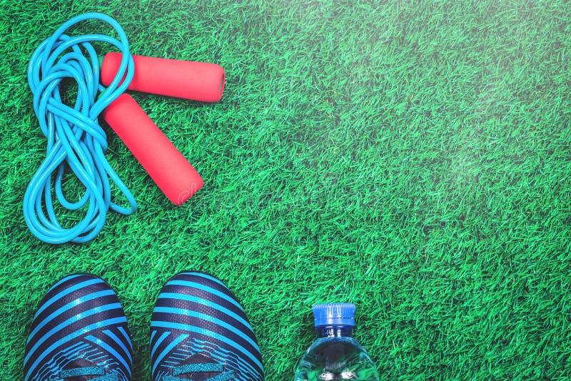 Прыгая веревочка, бутылка с водой и зажимы против зеленой искусственной дерновины стоковые изображения