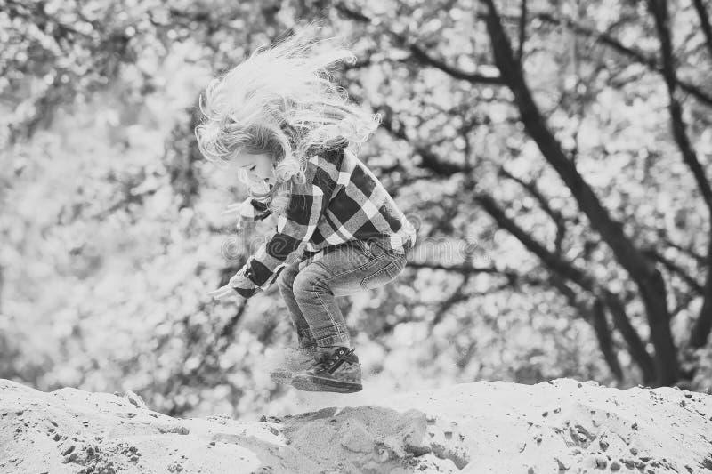 Прыжок ребенка на песке весной или парке лета стоковое фото rf