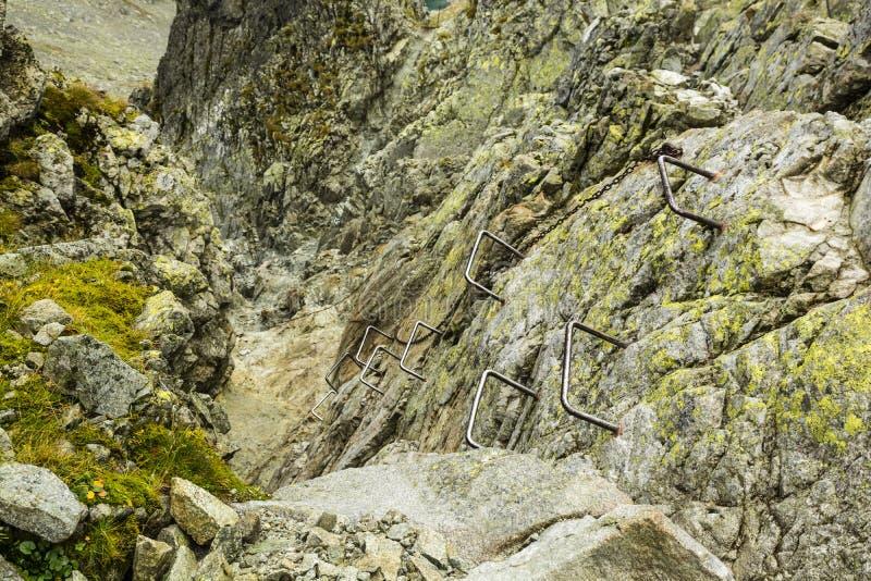 Пряжки металла и цепь, который нужно помочь вам преодолевать крутую и более трудную часть следа в горах стоковая фотография