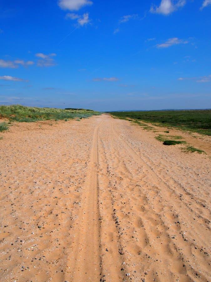 Прямая длинная сухая дорога песка со следами автошины и следы ноги удлиняя к горизонту окруженная травой покрыли дюны с br стоковые изображения