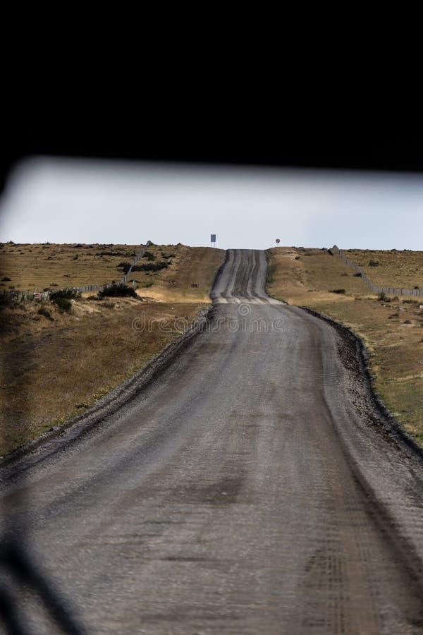прямая замотка дезертировала дорогу, увиденное до конца окно лобового стекла шины, в дезертированном ландшафте в Патагонии стоковая фотография
