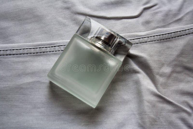 Прямоугольный флакон духов на свете - серых джинсах стоковая фотография rf