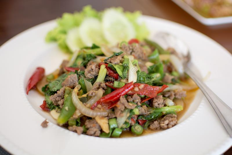 Пряная зажаренная свинина с листьями базилика в белом блюде, тайском меню стоковое фото rf
