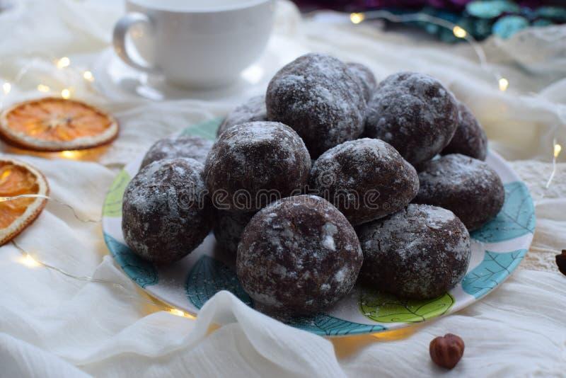Пряник шоколада, взбрызнутый с напудренным сахаром на плите с листьями бирюзы, высушенный апельсин стоковое фото