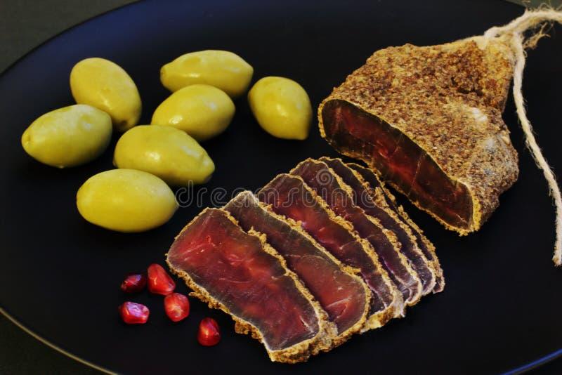 Пряное вкусное ароматичное отрывистое с красными семенами гранатового дерева и большими зелеными оливками на черной керамической  стоковая фотография rf
