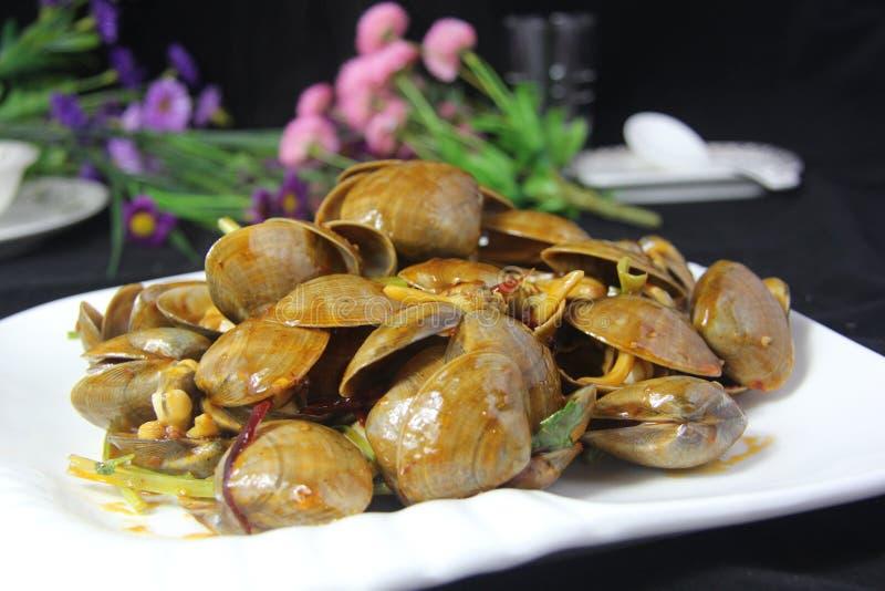 Пряные clams с овощем на белой плите в черной предпосылке стоковая фотография rf