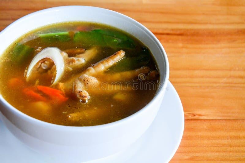 Пряный и кислый суп Том ног цыпленка Yum в белом керамическом шаре на предпосылке деревянного стола, космосе экземпляра стоковое фото rf