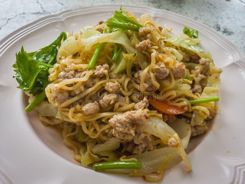 Пряный салат немедленной лапши с луком в белой плите на таблице Выберите фокус стоковые изображения