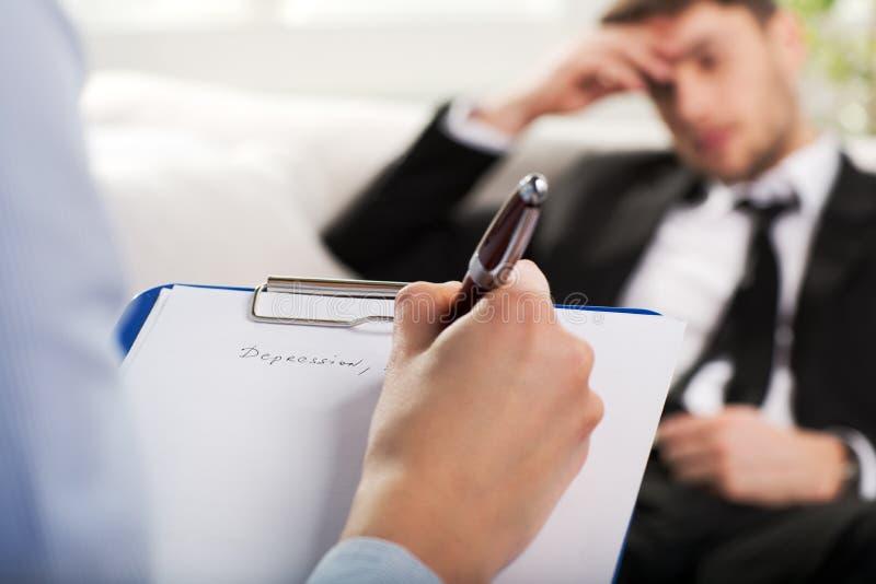 Психиатр рассматривая мужского пациента стоковая фотография rf
