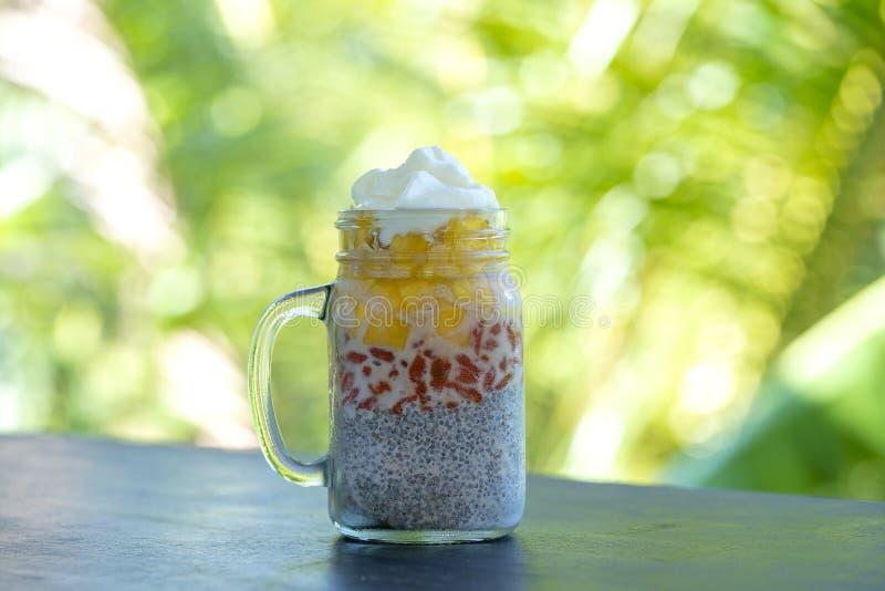 Пудинг chia молока миндалины со свежим желтым манго и красными ягодами goji в стеклянной кружке опарника Семена Chia завтрака Veg стоковая фотография