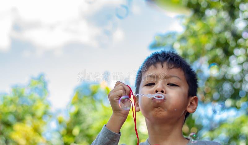 Пузыри мальчика Азии портрета дуя в саде стоковые фото