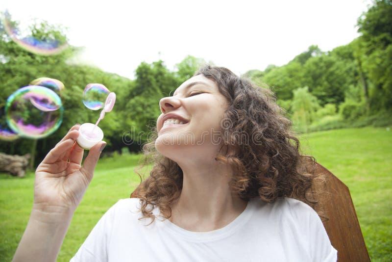 Пузыри молодой женщины дуя стоковое изображение