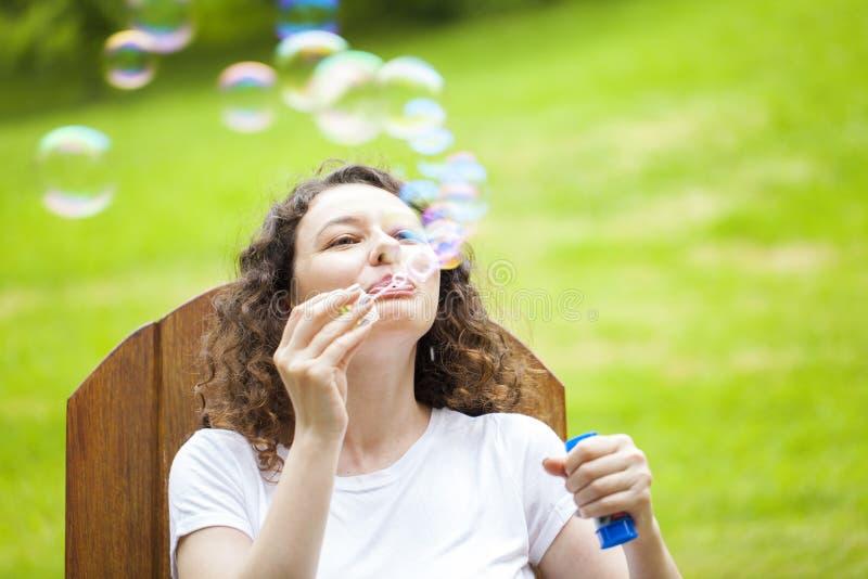 Пузыри молодой женщины дуя стоковые изображения